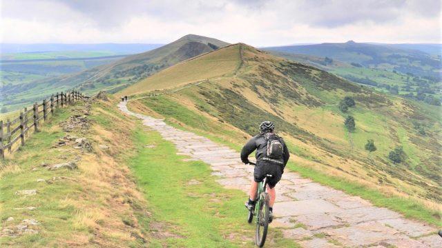 Man mountain biking along ridge